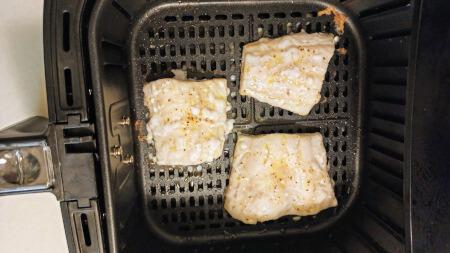 tres trozos de bacalao en cesto de freidora sin aceite