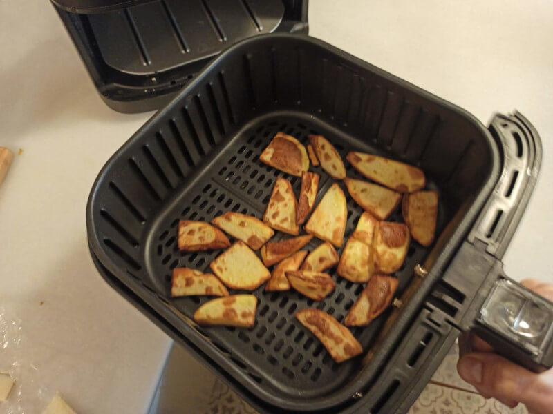removemos las patatas fritas en el cesto de la freidora de aire
